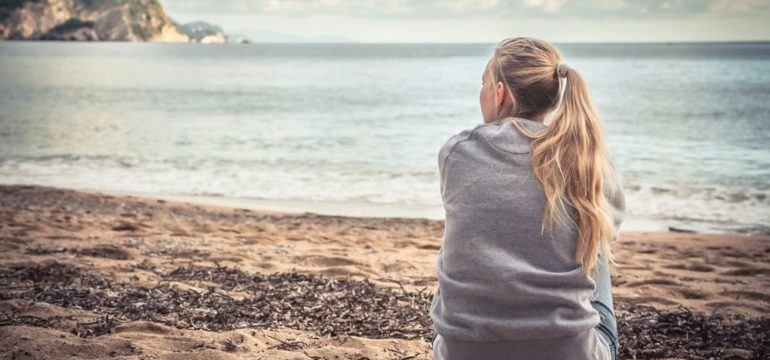 Female sitting on beach looking into the distance