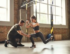 Personal trainer assisting client on the TRX machine