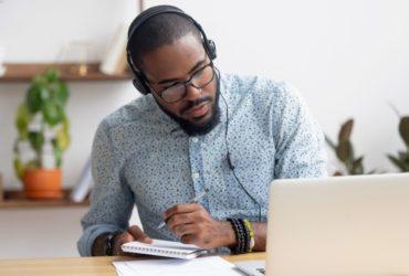 Man using laptop and taking notes