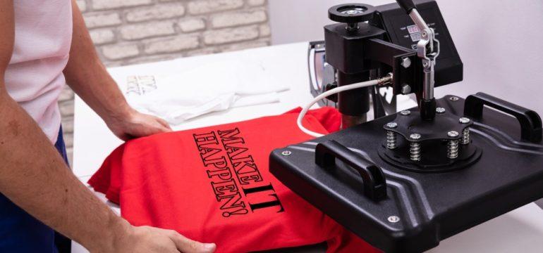 Man pressing print onto a red t-shirt