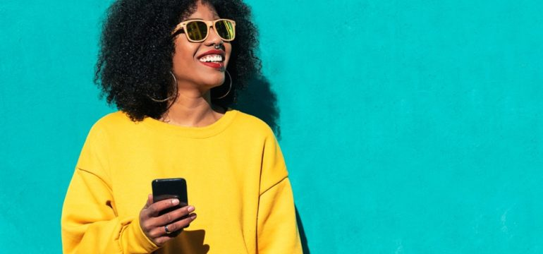Woman wearing a yellow jumper and holding a phone posing against an aqua background
