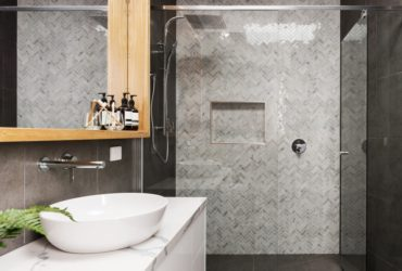 Bathroom renovation with grey herringbone tiles on the shower feature wall