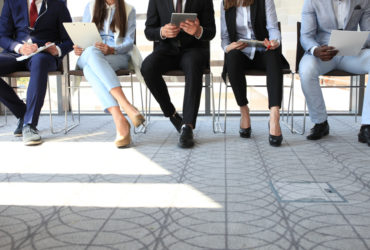 Group of five people sitting down in professional attire awaiting a job interview