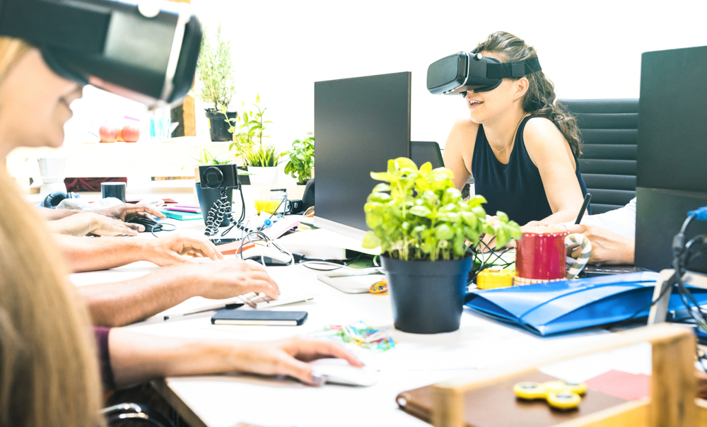 A group of females wearing a black headset over their eyes whilst at their desk