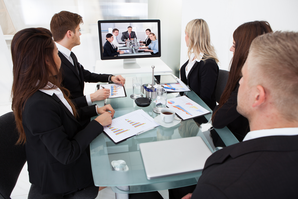Group of business people at a table observe a screen with other people on it
