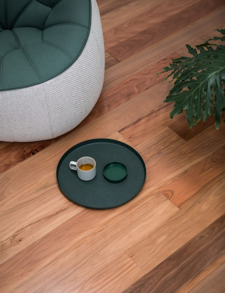 Top view of a timber floor with a chair and coffee on the ground