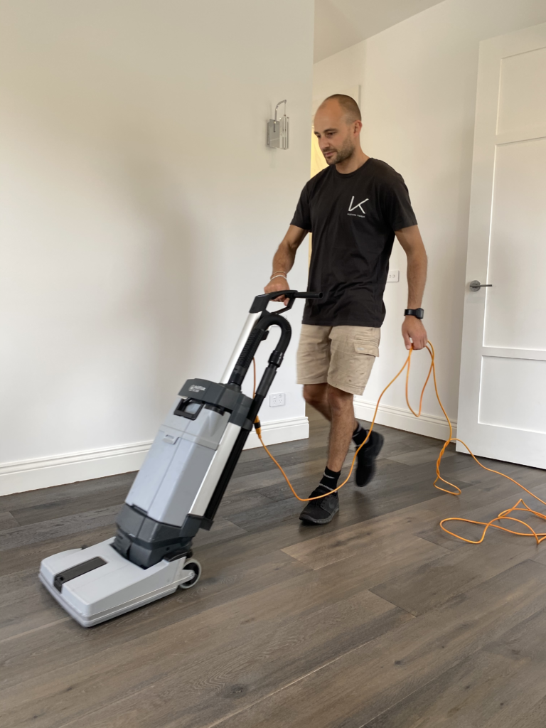 Man using a large cleaning device on a timber floor