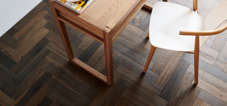 Zoomed in aerial view of a hardwood timber floor with table and chair