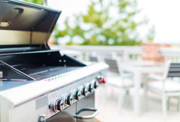 Large silver barbecue on the balcony of a home