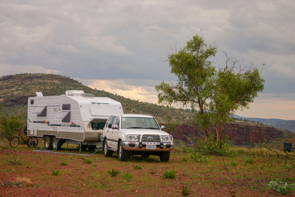 Large caravan being towed by a four wheel drive through the Australian outback.
