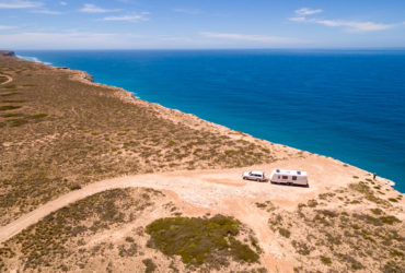 Aerial view of a caravan and car on a desert road near the ocean.