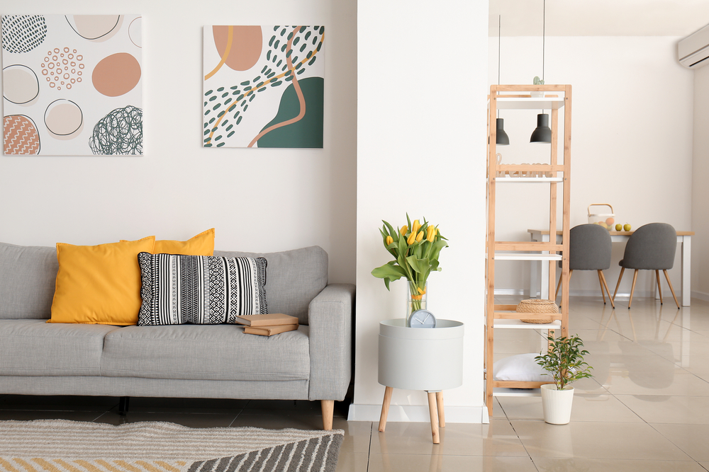 Grey couch in a living room with two paintings on the wall
