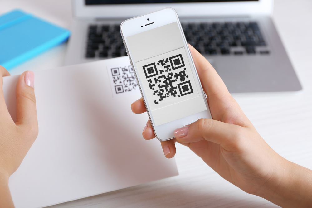 Person scanning a qr code from a piece of paper on their phone