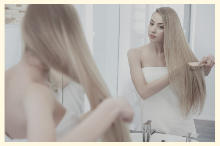 Lady in towel blow drying her hair in the mirror