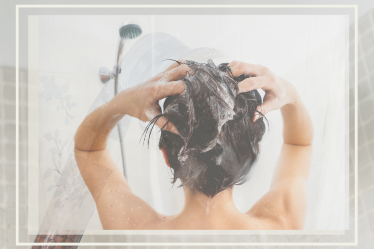 Person facing showerhead rubbing hair with soap