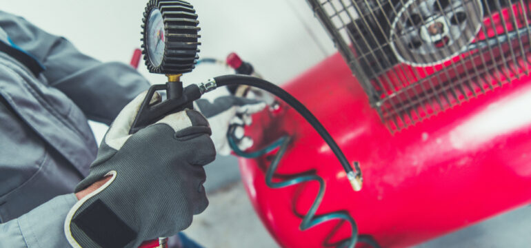 Person holding black temperature gauge that is connected to a red air compressor