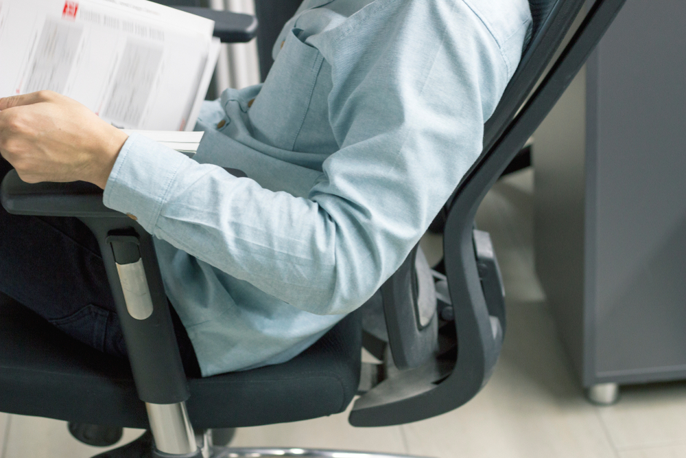 Person in light blue collared shirt leaning back on office chair whilst reading paper