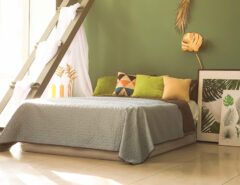 Large bed with against a green wall with colourful pillows and paintings on the ground