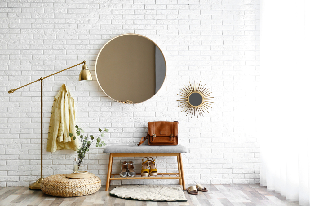 Painted white brick wall with circular mirror, padded chair and gold standing lamp