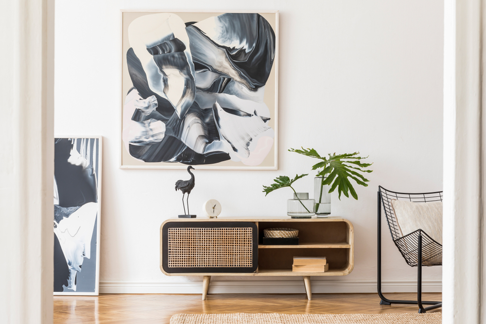 Plain white wall with large poster, retro table with plants on it