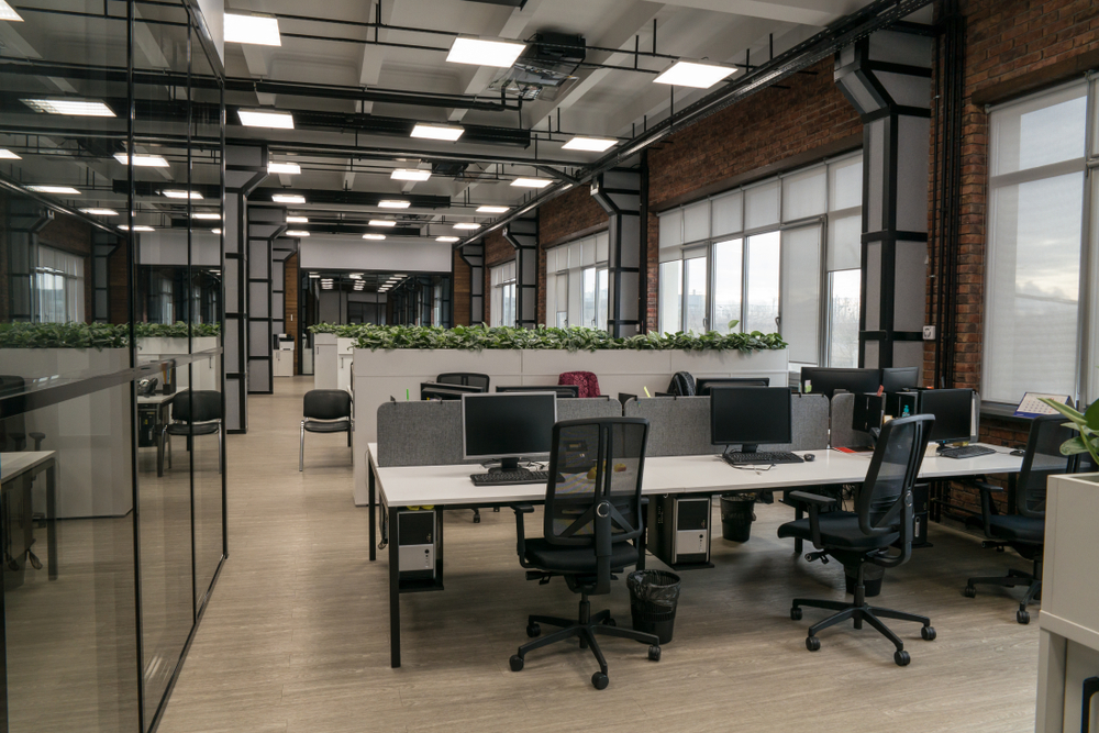 A modern office with a row of white desks and chairs