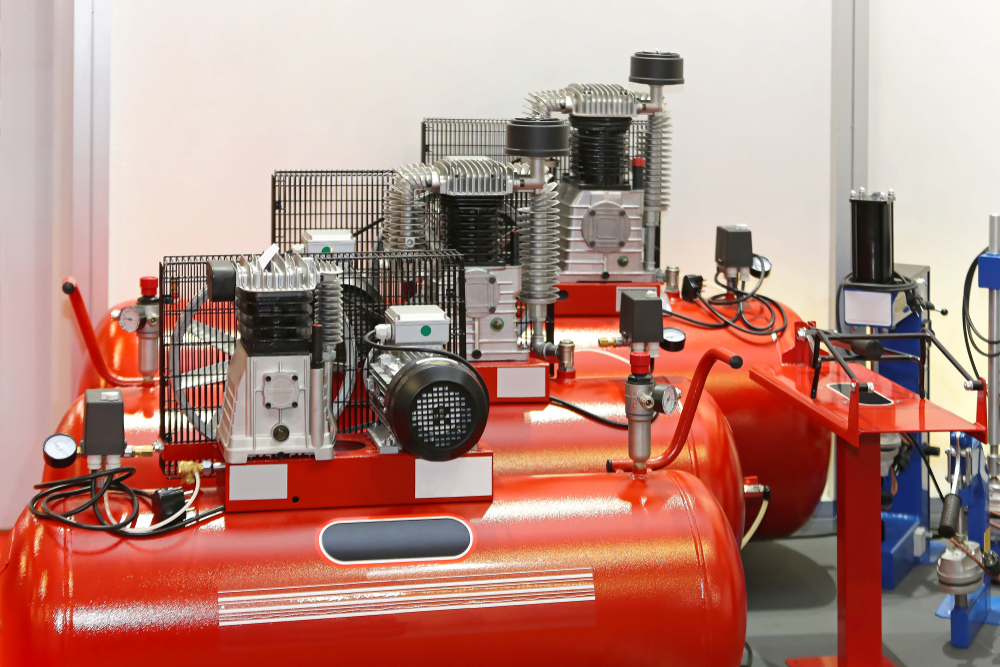3 large air compressors in a garage