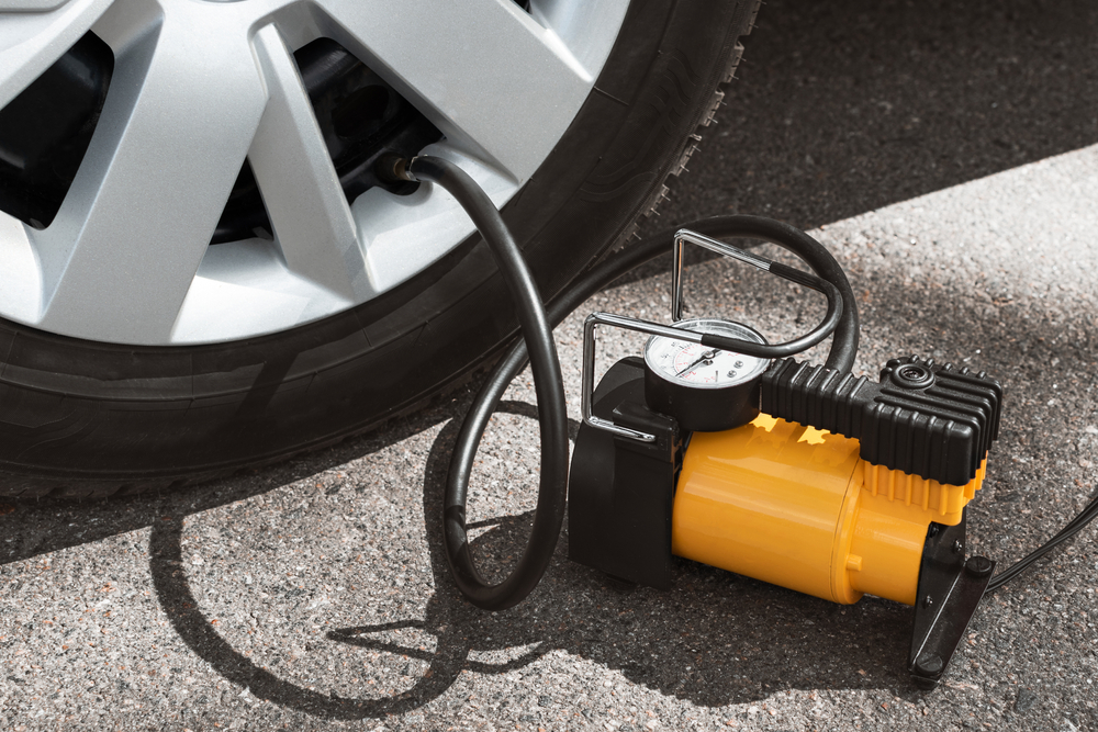 Yellow portable air compressor being used on a car tyre