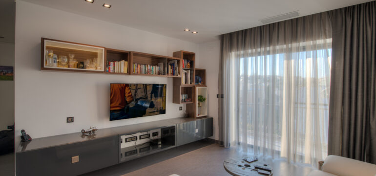 Large living room with a wall mounted TV