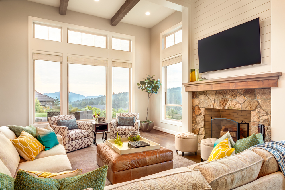 Wall mounted TV above a fireplace in an open living room